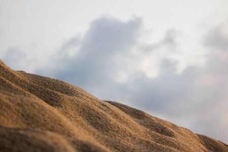 A close-up of the sand dunes has a gray sky as the background.