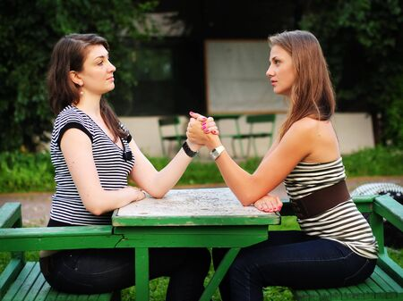 Two girls doing arm-wrestling Stock Photo - 5417823