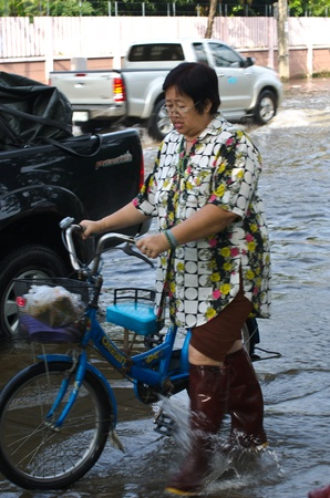 decades: BANGKOK, THAILAND-NOVEMBER 7: An unidentified women  are hand bicycle in a flooded street during the worst flooding in decades  on November 7, 2011  Nuan Chan Road, bangkok, Thailand. Editorial