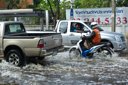 BANGKOK - NOVEMBER 7: Car and Motorcycle navigating through the flood after the heaviest monsoon rain in 20 years in the capital  on November 7, 2011  Nuan Chan Road, bangkok, Thailand.