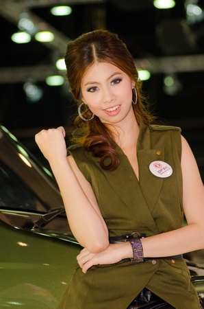 BANGKOK, THAILAND - DECEMBER 6: Unidentified female presenter at DFSK (Gong Feng) booth in THE 28th THAILAND INTERNATIONAL MOTOR EXPO 2011 on December 6, 2011 in Bangkok, Thailand.