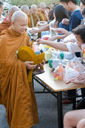 BANGKOK, THAILAND - JANUARY 8:Unidentified Bangkok people give food offerings for monks in new year day festival on Jan 8, 2012 at Baan Suan Thon village,Bangkok , Thailand