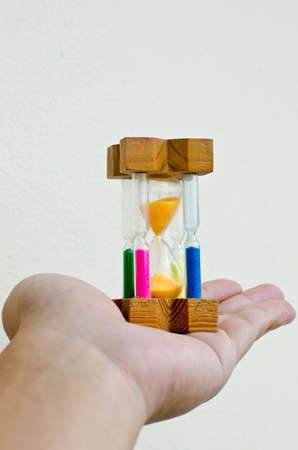 colorful sand hourglass timer in male hand on white background Stock Photo - 12058082