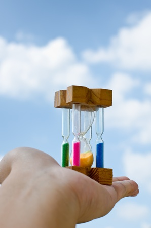 Colorful hourglass sand timer in hand of man on the sky