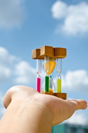 Colorful hourglass sand timer in hand of man on the sky Stock Photo - 12058077