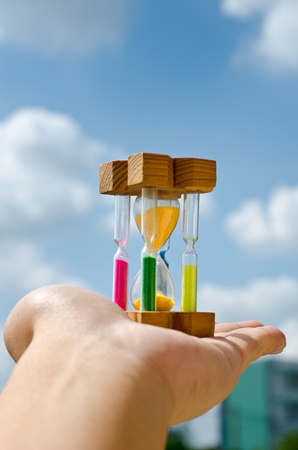 Colorful hourglass sand timer in hand of man on the sky Stock Photo - 12058085
