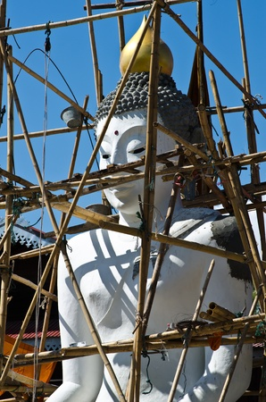 buddha image against blue sky,under construction. photo