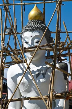 buddha image against blue sky,under construction. photo