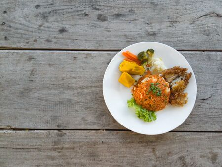 Fried rice, fried chicken  vegetables on a wooden table