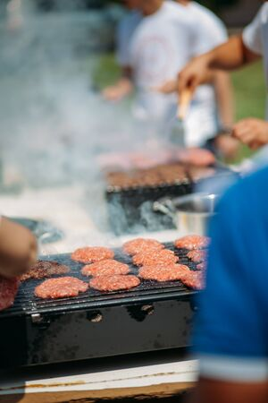 Burgers on a grill smoking. Outdoor summer barbeque