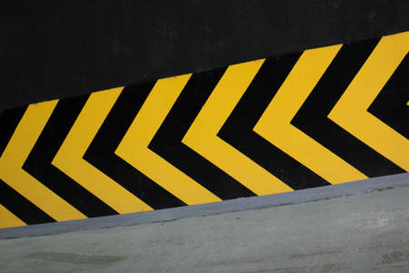 Yellow and black arrows pointing toward basement parking garage