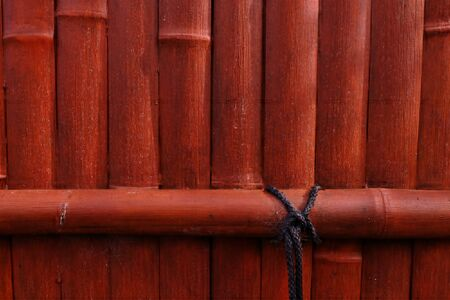 Orange Bamboo wall with black rope