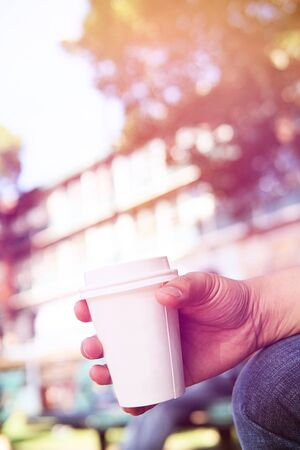 Close up of male hand holding take away coffee cup at morning time. Paper cup of takeaway coffee holding by a man with flare light.