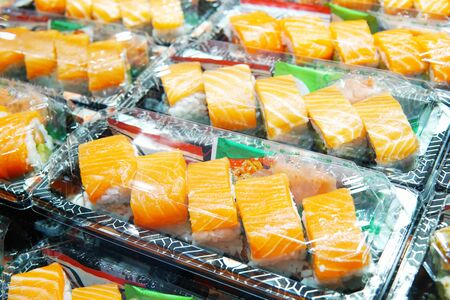 Selective focus on salmon sushi box. Salmon sushi in takeaway box ready for sale in restaurant. Sushi box with wasabi and ginger for hurry meal. Salmon sushi box cook in asian style