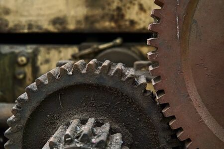 Grain Image: Close up of old machine factory made of steel and used in the past. Broken and rustic machine left over in abandon factory. Image of aged equipment with rust and gear part. Stock Photo