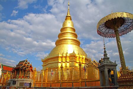 Golden pagoda on backdrop with cloud at Wat Phra That Hariphunchai , Lamphun Province, of Thailand  photo