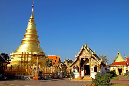 Golden pagoda and backdrop with blue sky at Wat Phra That Hariphunchai , Lamphun Province, of Thailand photo
