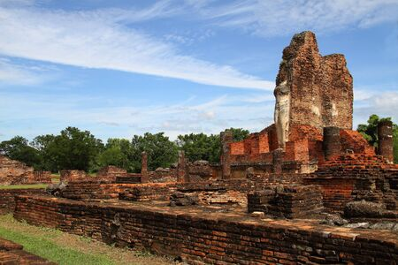Ancient ruins statue buddha stand  of Wat Phra Pai Luang in Sukhothai Historical park, Thailand  photo