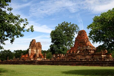 Ancient ruins and green grass of Wat Phra Pai Luang in Sukhothai Historical park, Thailand  photo