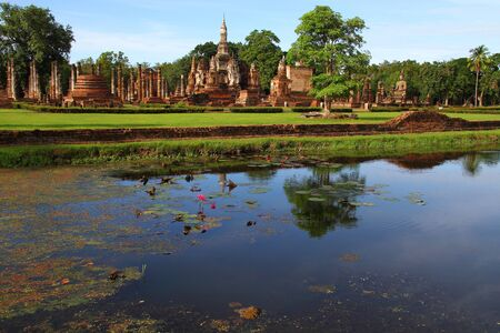 Canal with green grass and architecture of Wat Pra Mahathat in Sukhothai Historical park, Thailand  photo