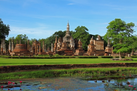 Field green grass and architecture of Wat Pra Mahathat in Sukhothai Historical park, Thailand  photo