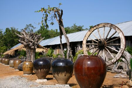 thialand: Old jar and wooden wheel whit blue sky at country of Thialand.