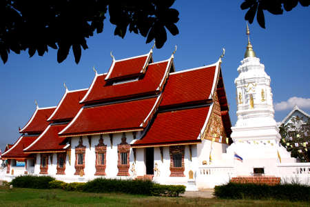 Red church and wihte pagota whit blue sky at Wat Sree Bunyoun Nan Province, Thailand photo