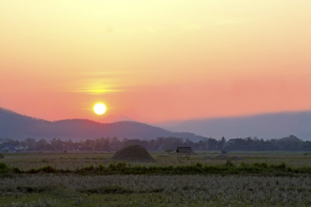 sward: The sunset at sward among hut and straw of farmer in village of Nan Thailand