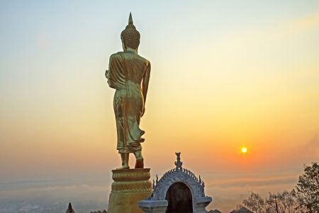 The sun shine to sculpture gold Buddha with field at countryside of Nan, Thailand photo