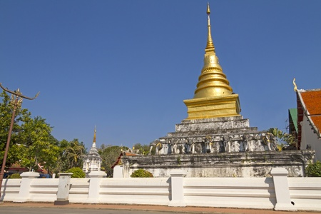 Blue sky outdoor with pagoda Wat Phra That Chang Kham, Nan,Thailand  photo