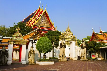 Three doll guard and architecture with blue sky at Wat Pho temple in Bangkok,Thailand  photo