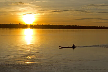 river county: The sunrise on Mekong River, and one small ship at Mukdahan county,Thailand Stock Photo
