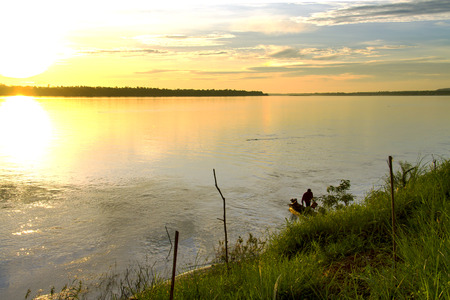 river county:  The man on Riverside Mekong River, beautiful with sunrise at Mukdahan county,Thailand