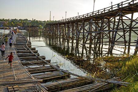 People and boy use bamboo bridge crossing river in Sangklaburi Kanchanaburi country, Thailand