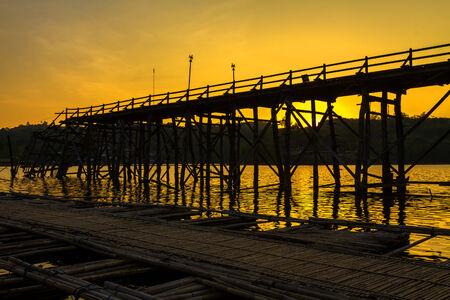 Silhouettes old wood bridge break in Sangklaburi Kanchanaburi country, Thailand  photo