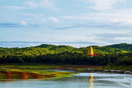 rains: Sharp gold pagoda on green river at sangklaburi, kanchanaburi, Province Asia thailand