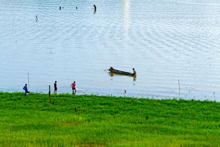 Green river and fisherman at sangklaburi, kanchanaburi, Province Asia thailand photo
