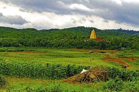 Gold pagoda and green nature at sangklaburi, kanchanaburi, Province Asia thailand photo