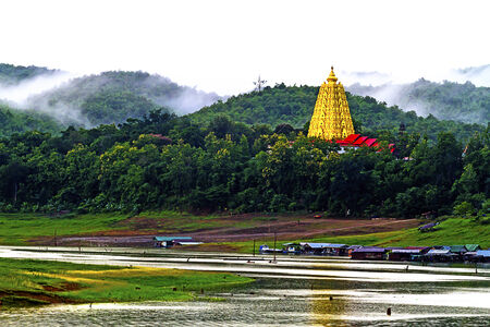 Gold pagoda morning rains at sangklaburi, kanchanaburi, Province Asia thailand photo