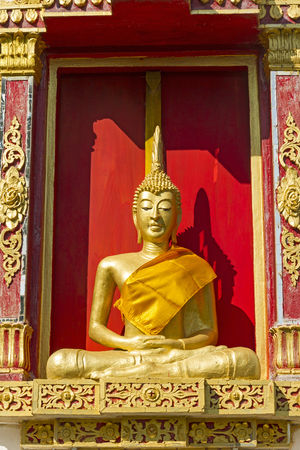 det: Gilded sculpture buddha sit in window at  Wat Som Det Temple, Sangkhla Buri, Kanchanaburi Province , Thailand