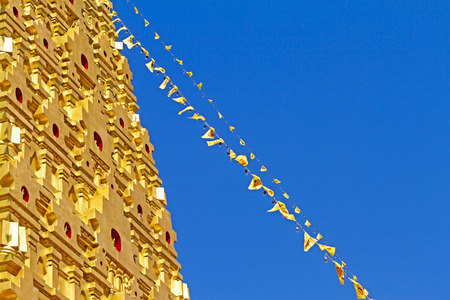 gaya: Gold pagoda and line flag at Wangvivagegaram Temple, Sangkhla Buri, Kanchanaburi Province , Thailand Stock Photo