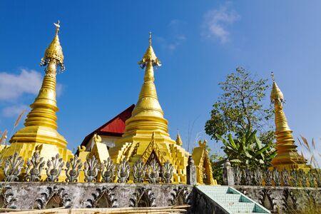 sangkhla buri: Three gilded sharp pagoda and blue sky at Wat Som Det Temple, Sangkhla Buri, Kanchanaburi Province , Thailand
