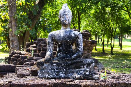 Old statue buddha outdoor green tree in Sisatchanalai Historical Park, Sukhothai province Thailand