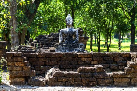 unesco: Old statue buddha with green background in Sisatchanalai Historical Park, Sukhothai province Thailand Stock Photo