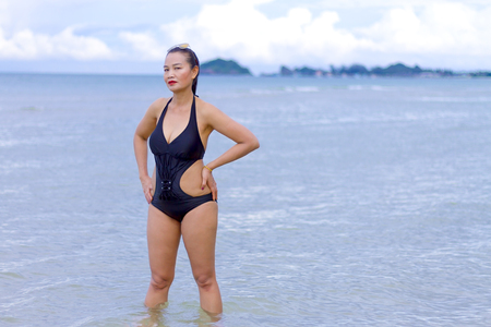 Woman black bikini show shape sexy symbol on beach at Ban Krut Beach, Prachuap Khirikhan Province Thailand Stock Photo