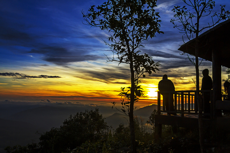Sunrise silhouette with two tourist at Phu Ruea Nation Park, Loei Province Thailand