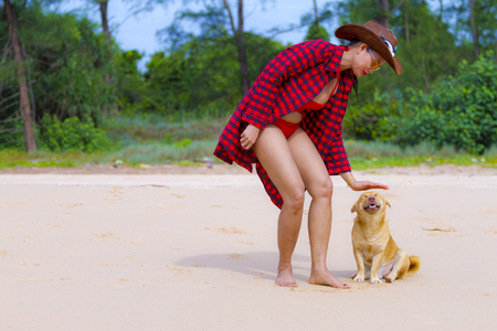 Woman and dog happy outdoor on beach at Bang Boet beach, Chumphion Province Thailand