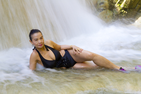 Woman and black bikini shape sexy in waterfall at Erawan Waterfall and  natural in Kanchanaburi province, Thailand
