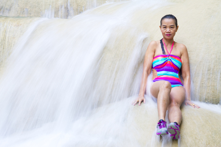 Woman happy on waterfall with bikini at Erawan Waterfall and  natural in Kanchanaburi province, Thailand
