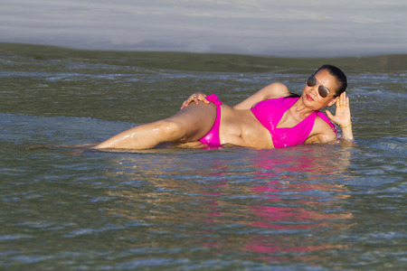 Woman relax with water on beach with pink bikini at Thung Wua Laen Beach, Chumphon Province Thailand Stock fotó